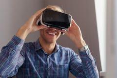 Gladlynt man som justerar VR-hörlurar med mikrofon Fotografering för Bildbyråer