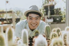 Gladlynt man som köper en kaktus arkivfoto