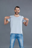 Gladlynt man som poserar i grå t-skjorta arkivfoto