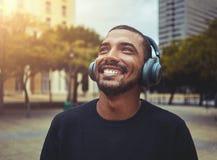 Gladlynt man som tycker om musik på den trådlösa headphonen royaltyfria foton
