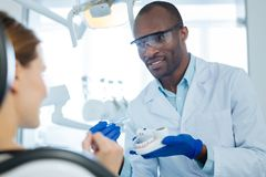 Gladlynt man som undervisar hans tålmodiga korrekta tand-borsta teknik Arkivbild