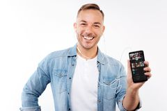 Gladlynt man som visar hans favorit- musik app royaltyfria bilder