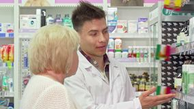 Gladlynt manlig apotekare som hjälper den äldre kvinnliga kunden lager videofilmer