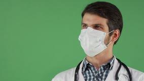 Gladlynt manlig doktor i en medicinsk maskering som ler till kameran royaltyfri bild