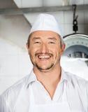 Gladlynt manlig slaktare In Butchery arkivfoto