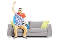 Gladlynt manlig sportfan med fotboll och den hållande ögonen på sporten för flagga Arkivfoton