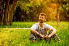 Gladlynt mansammanträde på gräs på parkera Arkivfoton