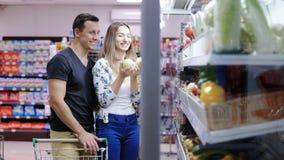 Gladlynt med vagnsplockning som ler i en supermarket lager videofilmer