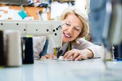 Gladlynt medelålders kvinnlig skräddare som använder symaskinen arkivfoton