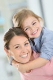 Gladlynt moder och dotter på henne tillbaka arkivfoto