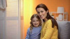 Gladlynt moder och liten dotter som ler och ser till kameran, annonsering arkivfoton