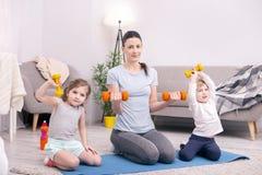 Gladlynt moder och ungar som utbildar med handvikter Arkivfoton