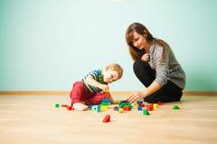 Gladlynt moder som spelar med hennes unge i sovrum royaltyfria foton