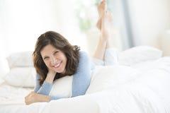 Gladlynt mogen kvinna som ligger i säng Arkivbild