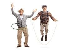 Gladlynt mogen man med ett hulabeslag och en hög man som hoppar på ett överhopprep arkivfoto