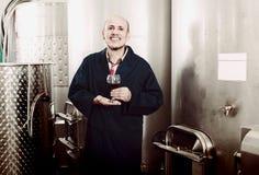 Gladlynt mogen manvinodlingarbetare som ser exponeringsglas av rött vin Royaltyfri Fotografi