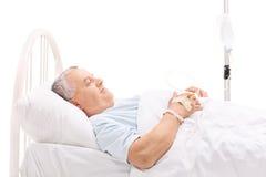 Gladlynt mogen patient som ligger i en sjukhussäng royaltyfria bilder