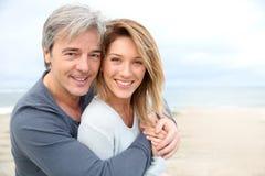 Gladlynt mogna par på stranden royaltyfri bild