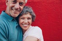 Gladlynt mogna par som omfamnar sig arkivfoto