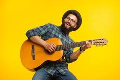 Gladlynt musiker med gitarren arkivfoto
