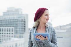 Gladlynt nätt blondin som utomhus använder minnestavlaPC Arkivbild
