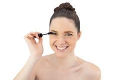 Gladlynt nätt modell som applicerar mascara Arkivbild
