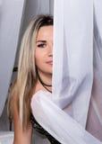 Gladlynt nätt sammanträde för ung kvinna på en säng bak gardiner och att le arkivfoton