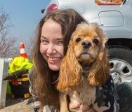 Gladlynt nätt ung kvinna i hatten som sitter och kramar hennes hund på stranden fotografering för bildbyråer
