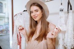 Gladlynt nätt ung kvinna som gör shopping i klädlager royaltyfri bild