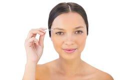 Gladlynt naturlig kvinna som använder pincett för hennes ögonbryn Arkivfoton