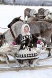 Gladlynt Nenets flicka i pälskläder med den nationella prydnaden Royaltyfri Fotografi