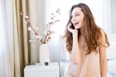 Gladlynt nätt ung kvinna som hemma talar på mobiltelefonen Royaltyfria Foton