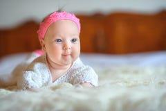 Gladlynt nyfött behandla som ett barn med en härlig rosa krona på huvudet, lögner på vit fluffig päls royaltyfri foto