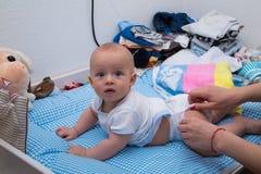 Gladlynt nyfött spela på blöjatabellen royaltyfri foto