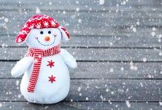 Gladlynt och rolig snögubbe i en röd hatt och en röd halsduk på en grå träbakgrund Fallande snötextur royaltyfria bilder