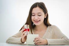 Gladlynt och upphetsad tonåring med gåvaasken Fotografering för Bildbyråer