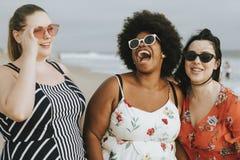 Gladlynt olikt plus formatkvinnor på stranden royaltyfri foto