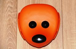 Gladlynt orange framsida av en mus på ett beige golv Arkivbild