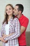 gladlynt par returnerar barn Kvinna och mankramar och kyssar på Royaltyfri Bild
