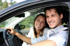 Gladlynt par som kör bilen Arkivbilder
