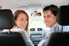 Gladlynt par som kör bilen fotografering för bildbyråer