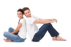 Gladlynt par som lyckligt ler på golv Arkivfoton