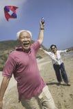 Gladlynt parflygdrake på stranden arkivbilder