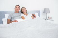 Gladlynt parkel i säng som ser kameran Arkivfoton