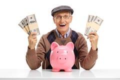 Gladlynt pensionär med packar av pengar och piggybank på tabellen arkivbilder