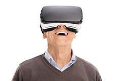 Gladlynt pensionär som använder en VR-hörlurar med mikrofon arkivfoto