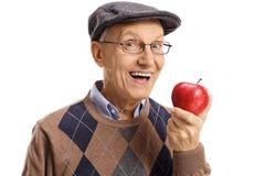 Gladlynt pensionär som har ett äpple royaltyfri bild