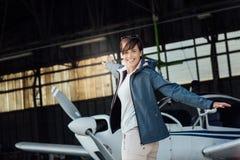 Gladlynt pilot- posera med ett litet flygplan royaltyfria foton