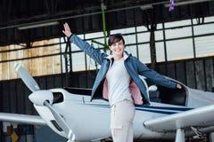 Gladlynt pilot- posera med ett litet flygplan royaltyfri fotografi