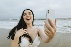 Gladlynt plus formatkvinnan som tar en selfie på stranden arkivfoton